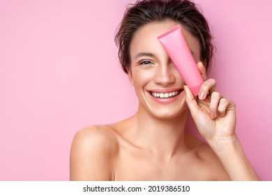 Smiling woman holds tube with cosmetic cream. Photo of attractive woman with perfect makeup on pink background. Beauty concept