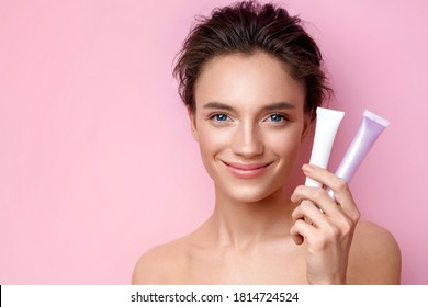 Smiling woman holds tubes with cosmetic cream. Photo of attractive woman with perfect makeup on pink background. Beauty concept