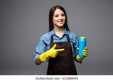 Smiling woman housewife pointing finger on cleaner bottle. Isolated.