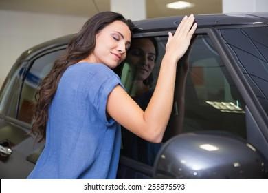 Smiling woman hugging a black car at new car showroom
