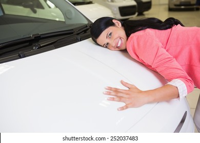 Smiling woman hugging a white car at new car showroom