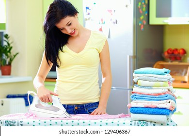smiling woman ironing clothes at home