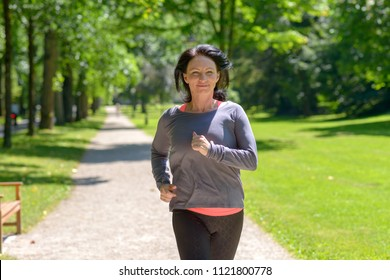 Smiling woman jogging towards the camera in a park  in a healthy active lifestyle concept