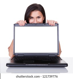 Smiling woman with just her eyes showing standing behind a blank laptop screen with copyspace for your advertising