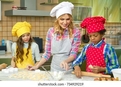 Smiling woman and kids, kitchen. Child making pastry.
