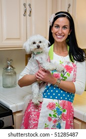 Smiling woman in kitchen holding cute white Maltese dog