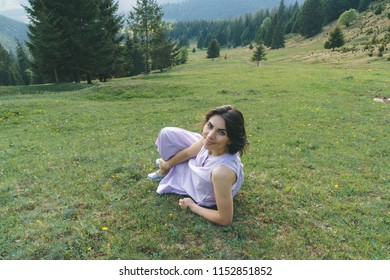 smiling woman laying on green grass at forest