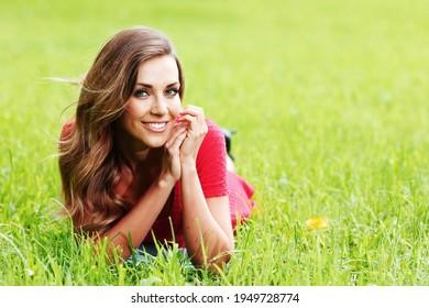 Lächelnde Frau, die auf grünem Frühling liegt und lächelt