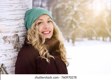 smiling woman leaning against birch tree enjoying sunny day in snow covered winter landscape, with sun flare light leak