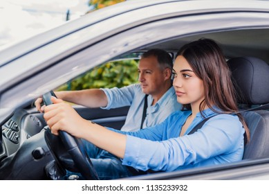 Smiling woman Learns to Drive in Car with instructor. Learning to Drive . Student driver taking driving test. Woman taking driving lessons from instructor