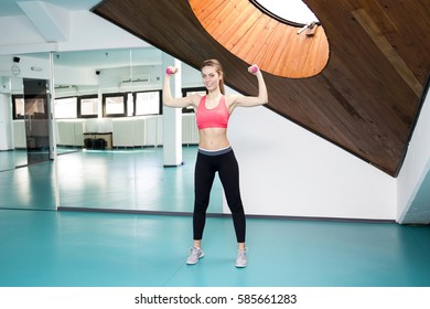 Smiling woman lifting weights and doing aerobics in gym