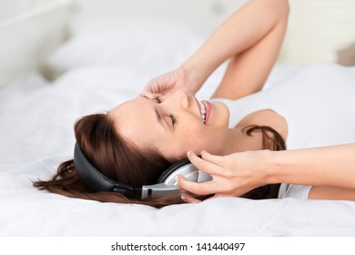 Smiling woman listening with headphone and lying on the bed