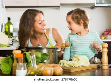 Smiling woman with little girl cooking at home kitchen