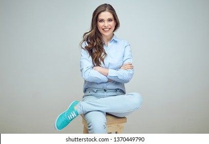 Smiling woman with long hair and crossed arms sitting on stool. isolated female portrait.