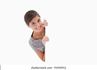 Smiling woman looking around the corner against a white background