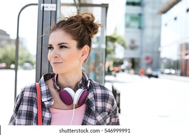 Smiling woman looking away while waiting at bus stop