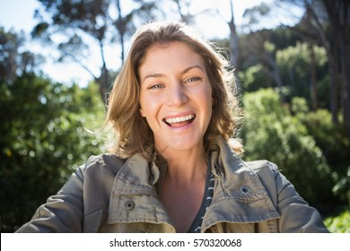 Smiling woman looking at camera in the countryside
