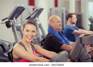 Smiling Woman Looking at Camera Using Recumbent Exercise Bike in Busy Gym