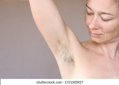 Smiling woman looking at her hairy unshaven armpit. Body positive and feminism concept, need to shave or depilation.