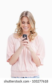A smiling woman is looking at her mobile phone against a white background