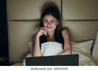 Smiling woman looking at laptop in dark room