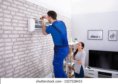 Smiling Woman Looking At Male Technician Repairing Air Conditioner With Screwdriver In Home