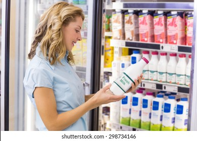 Smiling woman looking at a milk bottle in supermarket