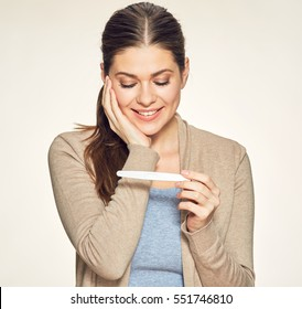 Smiling woman looking on pregnant test. Isolated portrait of young expectant mother.