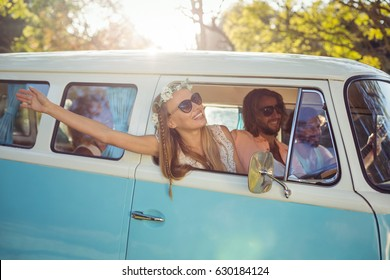 Smiling woman looking out of campervan window on a sunny day