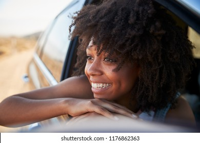 Smiling Woman Looking Out Of Car Window Enjoying Road Trip