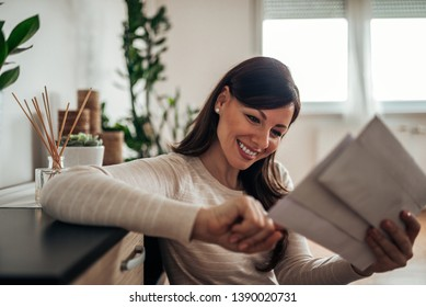 Smiling woman looking at received mail at home, close-up.