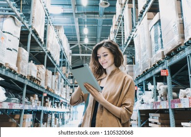 Smiling woman looking at a tablet pc computer in a trading warehouse