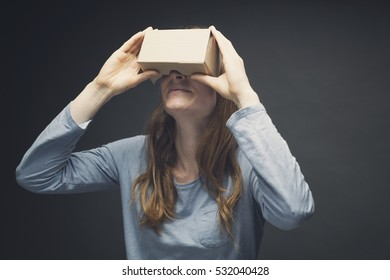 Smiling woman looking up through homemade VR goggles.