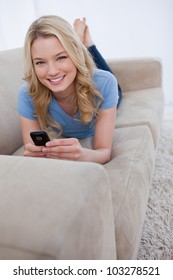 A smiling woman lying on a couch looking at the camera is holding a mobile phone