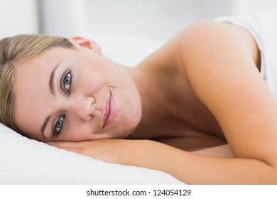 Smiling woman lying on her bed in the white bedroom