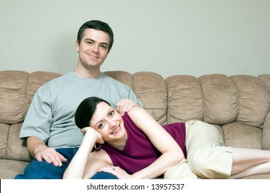 A smiling woman lying on a smiling man's lap sitting on a sofa.
