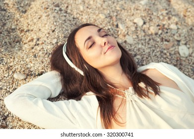 Smiling woman lying on a sea sand and listening music.