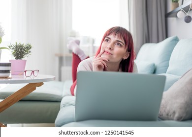 Smiling woman lying on sofa and using laptop while thinking and planning future at home