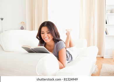 smiling woman lying on sofa reading a book in living room