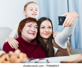 Smiling woman making selfie with mother and daughter at home