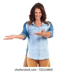 smiling woman with man hiding behind her welcomes you on white background
