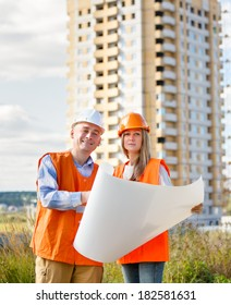 smiling woman and man working as architects background house against the sky