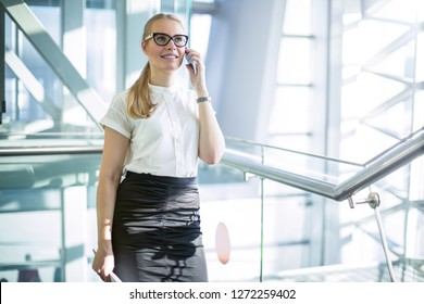 Smiling woman managing director having smartphone conversation with international partners while standing in corridor company during break at job. Cheerful female economist talking via cell telephone