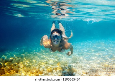 Smiling woman with mask underwater snorkeling in the clear tropical water