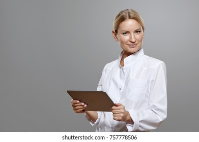 Smiling woman medic standing with tablet. Isolated on gray background.