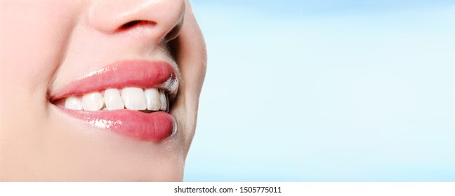 Smiling woman mouth with great white teeth on a blue background. Dental and medical concept