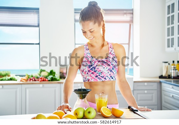 Smiling woman with muscular body standing near juicer in the kitchen. Horizontal indoors shot