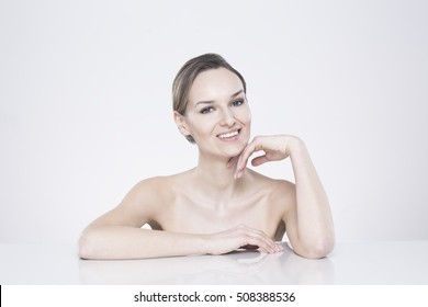 Smiling woman with naked body sitting behind the smooth tabletop