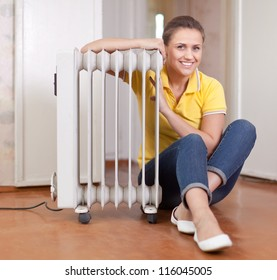 smiling woman  near warm radiator  in home