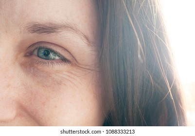 Smiling woman with no make up, blue eyes, brown hair and freckles. Showing crow's feet around the eyes.